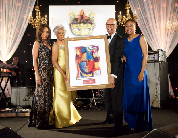 UNCF President Michael L. Lomax helps showcase the art for the live auction